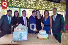 MARCELO AGUIRRE acompañado de su familia y padrinos cortando el pastel